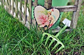 Heart-shaped picture hanging from frame of bench and gardening tool on lawn