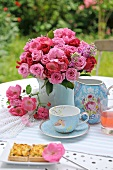 Tea and cake in garden with bouquet of roses in porcelain vase