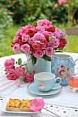 Kaffee und Kuchen im Garten mit Rosenstrauss in Porzellanvase