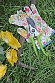 Cut roses next to gardening tools and gloves on lawn