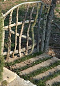 Home-made garden gate of unfinished branches and stone blocks set into garden path