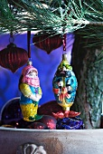 Baubles shaped like Oriental figures and lanterns hanging on Christmas tree