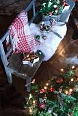 Christbaumdeko und weisses Fell auf rustikaler Bank neben geschmücktem Weihnachtsbaum