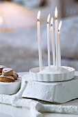 Lit candles stuck into heap of salt in dish on white-painted piece of wood next to pastries