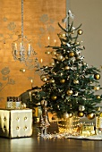 Christmas tree with gold decorations and fairy lights next to gold cube stool