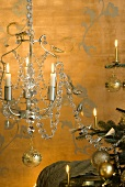 Chandelier and Christmas tree in front of gold wall with tendril-motif wall stickers