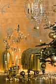 Gold Christmas decorations next to Christmas tree - fairy lights, candle arrangement, floor vase and stool
