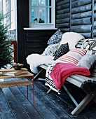 Sheepskins, cushions and blankets on wooden bench on terrace