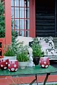 Gartentisch mit roten Keramik-Windlichtern und Edelweiß in Pflanzentöpfen