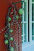 Branch of green apples wrapped with fairy lights decorating door