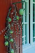 Zweig mit grünen Äpfeln umwickelt mit Leuchtzweigen als Türdeko