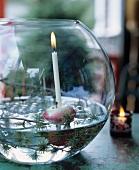 Lerchenzweige, Apfel und Kerze in einer Glaskugel