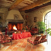 Inviting seating area with Provençal-patterned cushions on delicate metal sofas in front of imposing stone fireplace