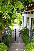 Geöffnetes Gartentor neben dem weiss gestrichenen Backsteinhaus