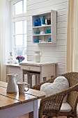 View across kitchen table and wicker chair of console table and small shelving unit on white wooden wall