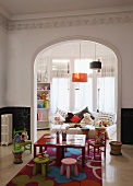 Colourful children's table and chairs in playroom with open doorway leading to child's bedroom