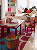 Colourful children's table and chairs; soft toys and cushions on bed in background