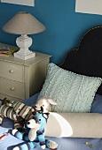 Stofftier, Nackenrolle und Kissen auf einem Bett, danben Kommode mit Lampe