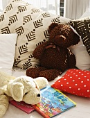 Soft toys, cushions and children's books on bed