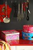 Colourful metal tins on red worksurface below kitchen utensils hanging against grey wall