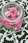 Glass jar filled with roses on floral, wrought-iron lattice surface
