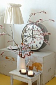 Branches of cherry blossom in vintage jug in front of station clock on old trunk