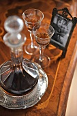 Glass decanter and liqueur glasses on antique wooden table