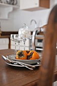 Place setting with persimmons on wooden table