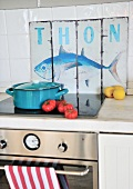 Light blue saucepan on cooker in front of vintage sign with fish motif