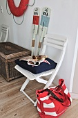 Boat house - fabric bag next to chair and paddles and lifebelt on wall