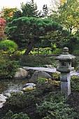 Asiatischer Garten mit japanischer Steinlaterne (Toro) neben Bachlauf