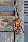 Rostiger Türbeschlag auf verwitterter Holztür