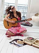 Woman sitting on platform playing the guitar next to retro record player on white floorboards