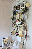 Metal rack of postcards hanging on a white wooden wall