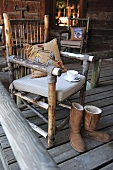 Home-made chair with cushioned seat and winter boots on wooden veranda