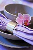 Place setting with a cloth napkin and silver napkin ring decorated with a violet flower