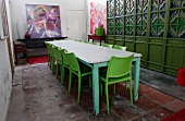 Long wooden table with peeling paint and green plastic chairs in front of wooden partition with stained glass windows in simple dining room