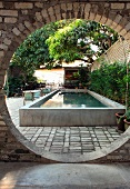 View of pool and garden chairs in planted courtyard through circular opening