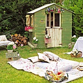 Idyllic picnic in garden with patchwork blanket and vintage fruit basket in front of shed decorated with flowers