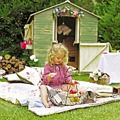 Blonde little girl sitting on patchwork blanket with wire basket of fruit; garden shed decorated with flowers in background