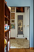 Shelving partition to one side of open doorway leading to hall with view of gallery of picture and Japanese wall hanging on interior door