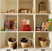 Toys and books in white shelving unit