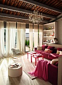 Elegant living room with pink sofa in front of large windows with floor-length curtains