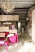 Rosa Polstersofa und pinkfarbener Couchtisch in offenem Wohnraum mit Küchenbereich