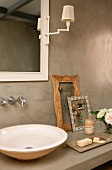 Vintage wooden frame next to washbasin on concrete surface below wall mirror