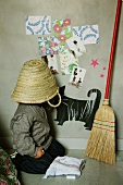 Child with straw basket on head sitting on floor next to besom leaning on wall with children's motifs