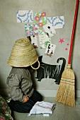 Kind mit aufgesetztem Strohkorb am Boden neben Besen an Wand mit beklebten Kindermotiven