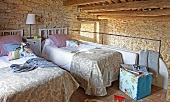 Twin beds on comfortable sleeping gallery with low wood-beamed ceiling and pale stone wall