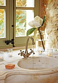 Romantic, Mediterranean bathroom - water running from retro tap fitting into curved marble basin