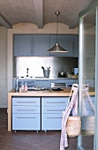 Youthful fitted kitchen with light blue fronts and stainless steel splashback; drawer units on castors below free-standing kitchen counter